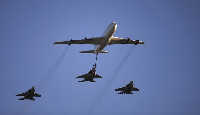 An Israeli Air Force Boeing 707 demonstrates refueling of an F15 fighter jet during a graduation ceremony for new pilots in the Hatzerim air force base near the city of Beersheba, southern Israel, Thursday, Dec. 25, 2014. (AP Photo/Tsafrir Abayov)