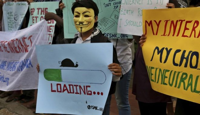 An activist wears a mask as he holds a placard during a demonstration supporting net neutrality, in Bangalore, India, Thursday, April 23, 2015. The principle of net neutrality is that online content be allowed to load at the same speed and forbids paid fast lanes favoring some content and says broadband providers can't slow Web traffic or block content. The Telecom Regulatory Authority of India last month put up a consultation paper on its website asking Internet users to give their views on net neutrality in India. The last day to vote for the campaign is April 24. (AP Photo/Aijaz Rahi)