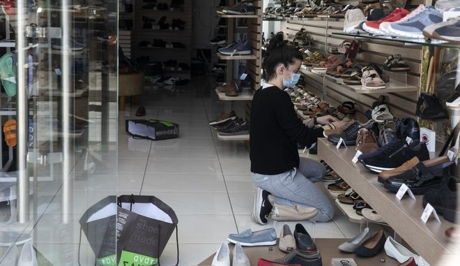 An employee, wearing a face mask to curb the spread of the coronavirus, adjusts shoes inside a shop, at Glyfada suburb west of Athens, Saturday, April 3, 2021. Greece has relaxed some coronavirus restrictions despite surging COVID-19 cases that are straining hospitals to their limits, with retail stores to reopen and people allowed to drive outside their home municipalities for exercise on weekends.  (AP Photo/Yorgos Karahalis)