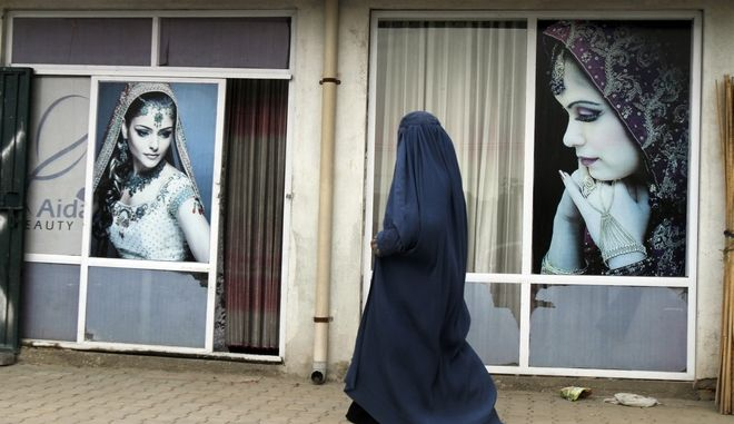 An Afghan woman wearing a Burqa, the all-covering dress worn by some Muslim women, walks past a beauty shop in, Kabul, Afghanistan, Monday, May 4, 2015. (AP Photo/Allauddin Khan)