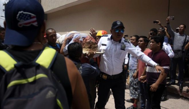 An injured woman is carried on a stretcher after being rescued in Cuernavaca, Morelos state, Mexico, Tuesday, Sept. 19, 2017. A magnitude 7.1 earthquake has stunned central Mexico, killing at least more than 100 people as buildings collapsed in plumes of dust. Thousands fled into the streets in panic, and many stayed to help rescue those trapped. (AP Photo/Tony Rivera)