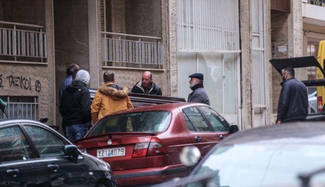 Άνδρες μεταφέρουν το φέρετρο με την σορό του άνδρα που βρέθηκε νεκρός στην είσοδο της πολυκατοικίας στου Γκύζη.