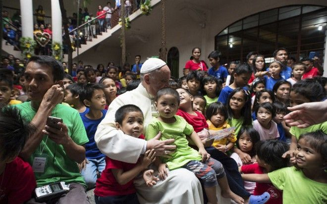 Pope Francis sits with children of the Anak-Tnk Foundation, founded in 1998 by a Jesuit priest, which helps homeless children and those living in the slums, in Manila's Intramuros district after celebrating Mass at the nearby Manila Cathedral, in Manila, Philippines, Friday, Jan. 16, 2015. Some 300 children at a Manila center for street kids got the surprise of their lives on Friday when Pope Francis showed up at their door. (AP Photo/Osservatore Romano, Pool)