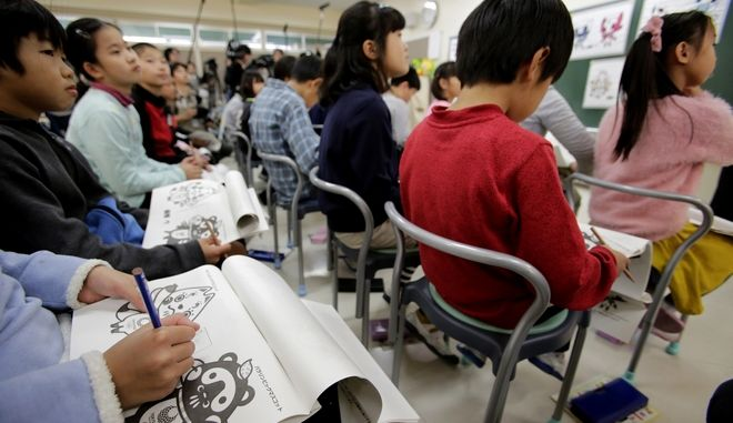 Elementary schoolchildren check three sets of candidates of official mascots for the Tokyo 2020 Olympics and Paralympics at their school in Tokyo Monday, Dec. 11, 2017. Voting by schoolchildren to select the official mascots began Monday across Japan. The results will be announced on Feb. 28. (AP Photo/Shizuo Kambayashi, Pool)