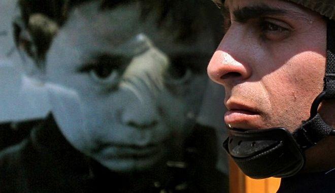 Ελληνοκύπριος στρατιώτης στέκεται μπροστά από τη χαρακτηριστική φωτογραφία του παιδιού που ψάχνει τους αγνοούμενους γονείς του στην Πράσινη Γραμμή
