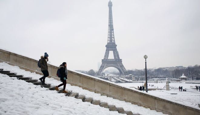People walk down a stairway with the Eiffel Tower in the background in Paris, Wednesday, Feb. 7, 2018. Heavy snowfall has caused major travel disruptions in the northern half of France and in Paris as the weather conditions caught authorities off guard. (AP Photo/Thibault Camus)