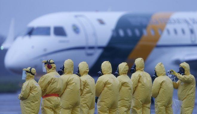 Αεροπλάνο που μεταφέρει ταξιδιώτες από την Γουχάν προσγειώνεται σε αεροδρόμιο.