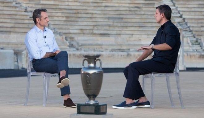 O πρωθυπουργός, Κυριάκος Μητσοτάκης συνομιλώντας με τον Τάκη Φύσσα, με φόντο το Παναθηναϊκό Στάδιο