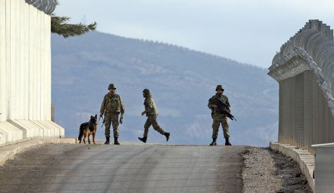 Turkish army soldiers patrol outside a military outpost near the town of Kilis, southeastern Turkey, close to the wall the country had been constructing to boost security along its border with conflict-stricken Syria, background, Thursday, March 2, 2017. Turkey's military is holding exercises along its border with Syria a week after Turkish troops and Syrian opposition forces captured the Islamic State-held town of al Bab in northern Syria. (AP Photo/Lefteris Pitarakis)