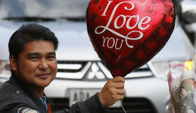 A man holds a balloon for a friend as they buy flowers for their loved ones in celebration of Valentine's Day, Tuesday, Feb. 14, 2017, in Manila, Philippines. Valentine's Day, associated with love and romance, is expressed with flowers, chocolates, balloons and dinner dates. (AP Photo/Bullit Marquez)