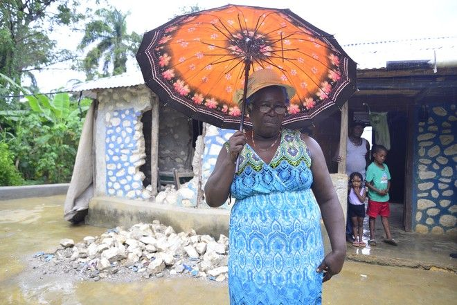 Η Estebelle στέκεται μπροστά από ό,τι απέμεινε από το σπίτι της, έχοντας πλέον μόνο την ομπρέλα της για προστασία από τη βροχή.