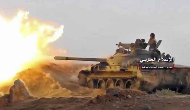 This frame grab from video provided Wednesday, Nov 8, 2017, by the government-controlled Syrian Central Military Media, shows a tank firing on militants' positions on the Iraq-Syria border. The United States and Russia are nearing an agreement on Syria for how they hope to resolve the Arab countrys civil war once the Islamic State group is defeated, officials said Nov. 9. (Syrian Central Military Media, via AP)