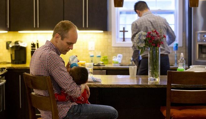 "SOCIAL VALUES: Gregg Pitts feeds his son Thomas Brunson-Pitts, 6 months, a bottle in the morning as his husband Brooks Brunson gets ready for work at their home in Washington, on Thursday, May 19, 2016. Married in 2013, Brooks Brunson and Gregg Pitts always knew they wanted to have a family together, and were delighted when they were able to start the adoption process for their son shortly after beginning to look for a match in 2015. The child's birth mother had no problem with a same-sex couple adopting the baby. ""We're an interracial same-sex couple family,"" says Brunson, ""But our day-to-day life is picking up dry cleaning, getting to work on time, making sure Thomas has his bottle prepared - we're the most boring people I know. But then when I take a step back I realize we are very unique. But I believe this is exactly where God wants me to be."" The District of Columbia legalized gay marriage in 2010. (AP Photo/Jacquelyn Martin)"