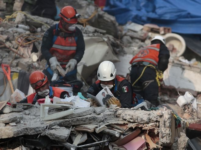 Rescue personnel look through a photo album as they work in rescue operations in the rubble of a building felled by a 7.1 magnitude earthquake, in the Ciudad Jardin neighborhood of Mexico City, Thursday, Sept. 21, 2017. Thousands of professionals and volunteers are working frantically at dozens of wrecked buildings across the capital and nearby states looking for survivors of the powerful quake that hit Tuesday. (AP Photo/Eduardo Verdugo)