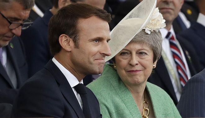 Η πρωθυπουργός του Ηνωμένου Βασιλείου Τερέζα Μέι δίπλα στον Γάλλο Πρόεδρο της Γαλλίας Εμανουέλ Μακρόν κατά τη διάρκεια εορτασμού της 75ης επετείου της απόβασης στη Νορμανδία