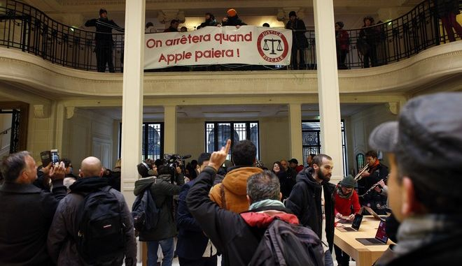 "Activists from anti-globalization organisation 'Attac' protest about allegations that Apple has avoided tens of billions of dollars in taxes by using overseas havens, in an Apple store, in Paris, Saturday, Dec. 2, 2017. Banner reads ""We will stop when Apple pays"". (AP Photo/Thibault Camus)"