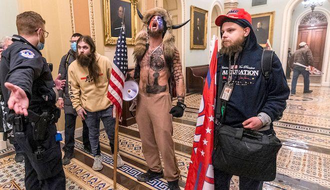 Υποστηρικτές του Τραμπ έρχονται αντιμέτωποι με άπραγους σχεδόν αστυνομικούς έξω από την αίθουσα της Γερουσίας μέσα στο Καπιτώλιο, 6 Ιανουαρίου 2021 στην Ουάσινγκτον.