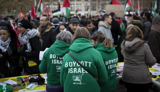 """Demonstrators wear shirts reading """"Boycott Israel"""" during a protest against President Donald Trump's decision to recognize Jerusalem as Israel's capital at Republique Square in Paris, France, Saturday, Dec. 9, 2017. (AP Photo/Kamil Zihnioglu)"""