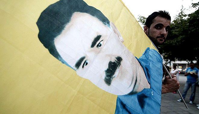 Κούρδος της Αθήνας με σημαία που έχει το πρόσωπο του Οτσαλάν