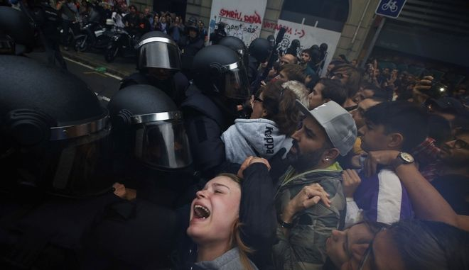 A girls grimaces as Spanish National Police pushes away Pro-referendum supporters outside the Ramon Llull school assigned to be a polling station by the Catalan government in Barcelona, Spain, early Sunday, 1 Oct. 2017. Catalan pro-referendum supporters vowed to ignore a police ultimatum to leave the schools they are occupying to use in a vote seeking independence from Spain. (AP Photo/Emilio Morenatti)