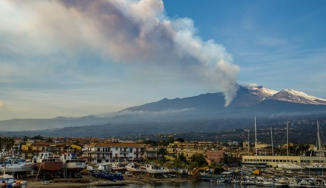 Smoke billows from the Mt Etna volcano as seen from Riposto, Sicily, Friday, Feb. 19, 2021. Europe's most active volcano remains active scattering ashes around a vastly populated area on its slopes. (AP Photo/Salvatore Allegra)