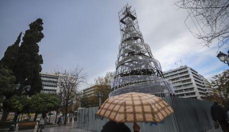 Κόσμος περπατά στην πλατεία Συντάγματος κρατώντας ομπρέλες για να προστατευτεί από τη βροχή