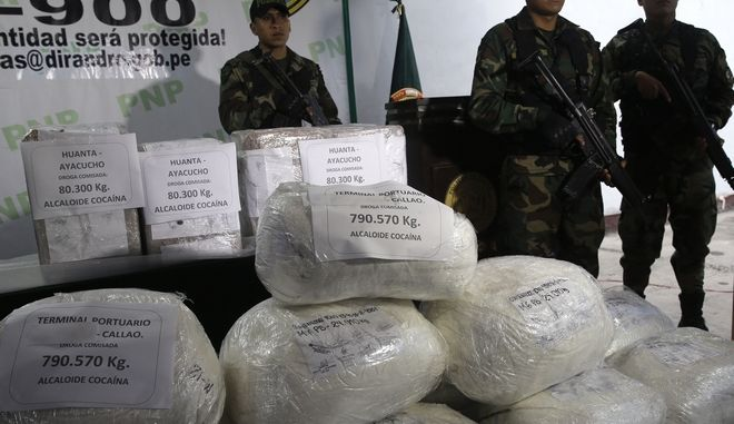 Police officers stand guard next to a bags of seized cocaine during a presentation at a police base in Lima, Peru, Wednesday, June 14, 2017. According to police more of two tons of cocaine were seized over the last weeks in several operations nationwide. (AP Photo/Martin Mejia)