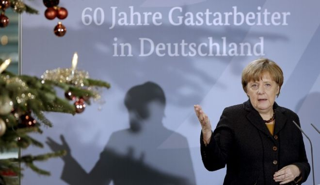 German Chancellor Angela Merkel delivers a speech during a reception at the chancellery in Berlin, Germany, Monday, Dec. 7, 2015 to mark the 60th. anniversary of the arrival of the first migrant workers in Germany. Slogan reads '60 Years of Migrant Workers in Germany'. (AP Photo/Michael Sohn)