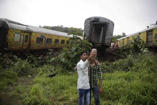 Νεαροί στην Ινδία φροντίζουν να βγάλουν selfie μπροστά στον συρμό που εκτροχιάστηκε περίπου 70 χλμ έξω από την Βομβάηα