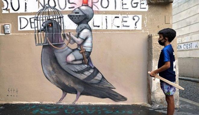 Σε τοίχους του Παρισιού της πανδημίας, παιδιά παίζουν φορώντας κράνη ιπποτών