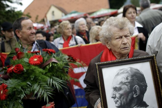 A woman carries a photo of Josip Broz Tito, the late Yugoslav Communist dictator, in Kumrovec, some 45 kilometers (29 miles) northwest of Zagreb, Croatia, Saturday, May 25, 2013. In Kumrovec, the birthplace of Tito, thousands gathered Saturday to mark his birthday and pay their respects to him and the ex-federation that fell apart in a cascade of ethnic wars more than 20 years ago. (AP Photo/ Marko Drobnjakovic)