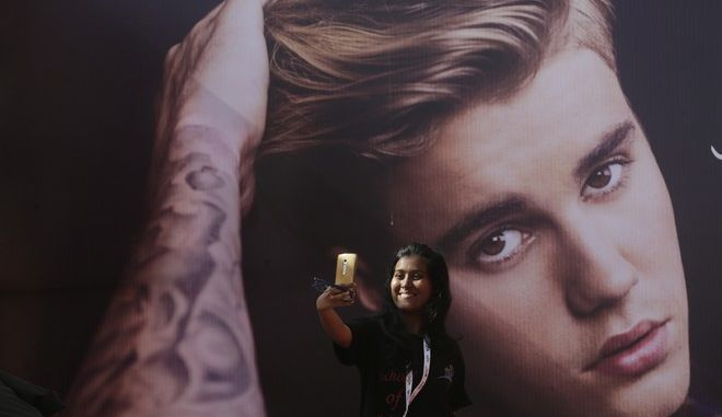 A fan of Canadian singer Justin Bieber takes a selfie in front of his poster ahead of a concert by him in Mumbai, India, Wednesday, May 10, 2017. (AP Photo/Rafiq Maqbool)