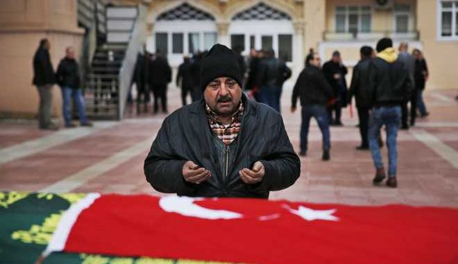 A man prays in front of the Turkish flag draped coffin of Muzaffer Aydemir, an 84-year-old tailor, killed in a rocket attack Wednesday night, during the funeral procession for the two victims of the attack, in the town of Kilis, Turkey, near the border with Syria, Thursday, Jan. 25, 2018. Two rockets fired from inside Syria hit the mosque during evening prayers and a house wounding at least 13 people. It was the latest in a series of rocket attacks against the Turkish border since Ankara launched a military offensive into Afrin to clear it of Syrian Kurdish militiamen whom it considers to be linked with Turkey's own Kurdish insurgents. (AP Photo/Lefteris Pitarakis)