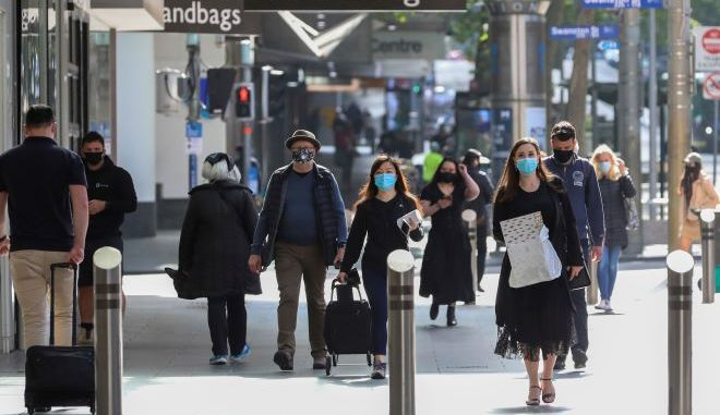 Άνθρωποι με μάσκες περπατούν στη Μελβούρνη της Αυστραλίας