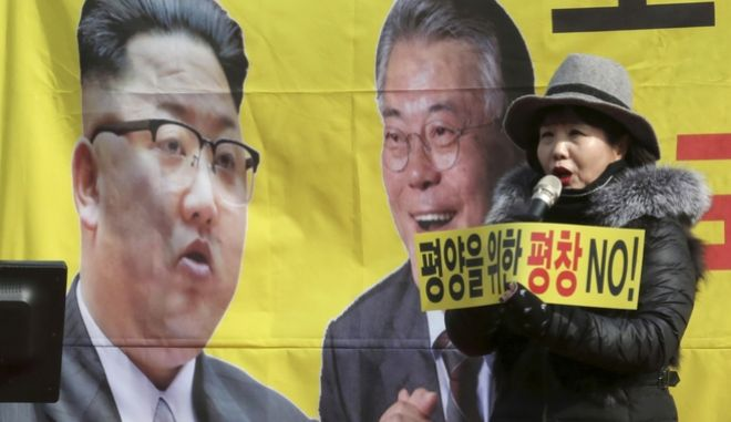"""A protester speaks in front of the portraits of South Korean President Moon Jae-in, right,  and North Korean leader Kim Jong Un, left, during a rally against North Korea's participation in the 2018 Pyeongchang Winter Olympics in Seoul, South Korea, Saturday, Feb. 10, 2018. Moon on Saturday met with senior North Korean officials including leader Kim Jong Un's sister Kim Yo Jong, over lunch at Seoul's presidential palace in the most significant diplomatic encounter between the rivals in years. The signs read: """"Pyeongchang for Pyongyang."""" (AP Photo/Ahn Young-joon)"""