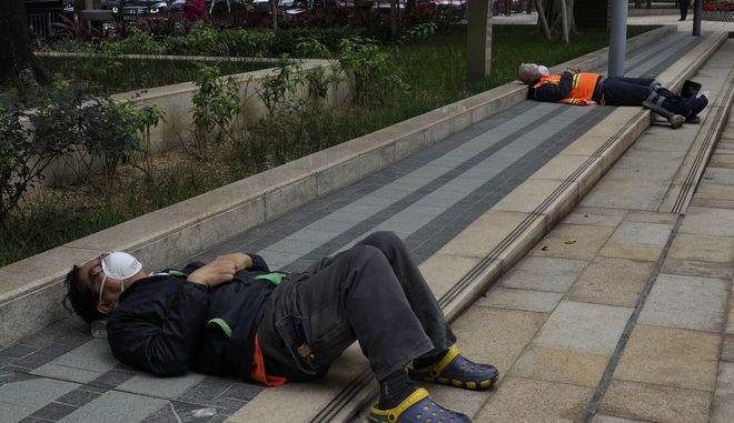 Εργαζόμενοι φορούν προστατευτικές μάσκες προσώπου καθώς ξεκουράζονται σε ένα πάρκο στο Χονγκ Κονγκ, τη Δευτέρα, 3 Φεβρουαρίου 2020