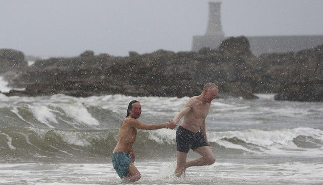 Hardy swimmers brave the snowy conditions at King Edwards bay near Tynemouth, England, following heavy overnight snowfall which has caused disruption across Britain, early Tuesday Feb. 27, 2018.  Many areas of the UK have seen a blanketing of snow, with police forces reporting treacherous driving conditions as temperatures have plummeted. (Owen Humphreys/PA via AP)
