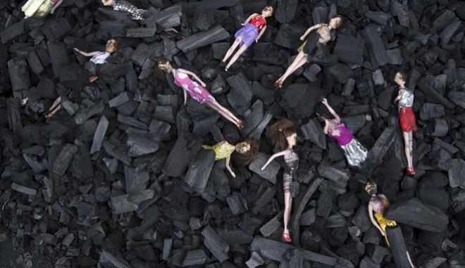Charred-stained dolls placed on a bed of charcoal are part of artists installation placed at the front gate of Presidential House, in remembrance of the victims of a fire at a youth shelter in Guatemala City, Thursday, March 9, 2017. Hospital officials say the death toll in the Wednesday morning fire at the Virgin of the Assumption Safe Home has risen to 28 after several more girls died overnight of severe burns. (AP Photo/Luis Soto)