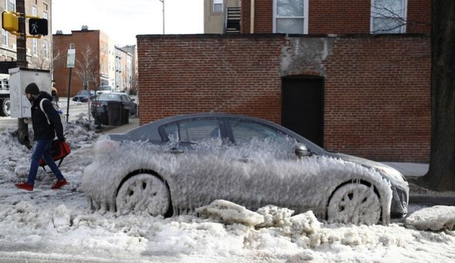 A car is partially covered by ice following an overnight water main break in Baltimore, Wednesday, Jan. 3, 2018. (AP Photo/Patrick Semansky)