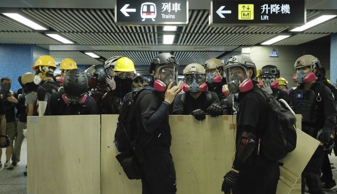 Protesters with makeshift shields pass through a subway station on their way to a police station in Hong Kong on Sunday, Aug. 4, 2019. Demonstrators in Hong Kong moved en masse to a luxury shopping district Sunday evening after riot police used tear gas to clear out an area they were previously occupying, as the 2-month-old protest movement showed no signs of easing. (AP Photo/Kin Cheung)