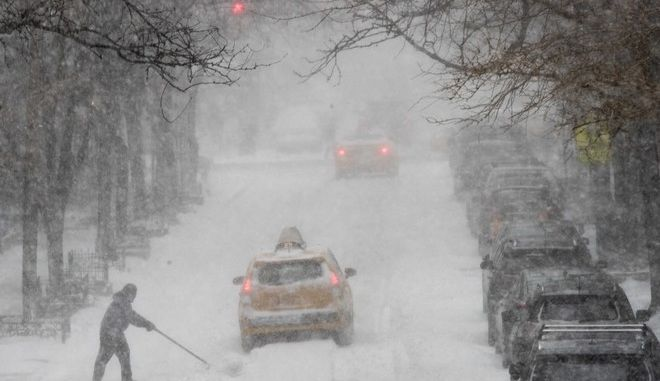 A man shovels snow as traffic makes it's way east on 81st street, Thursday, Jan. 4, 2018, on the Upper East Side of Manhattan. A massive winter storm swept from the Carolinas to Maine on Thursday, dumping snow along the coast and bringing strong winds that will usher in possible record-breaking cold. (AP Photo/Mary Altaffer)