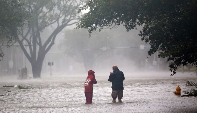 A television news crew wades into a flooded street in the Brickel section of Miami as Hurricane Irma passes by, Sunday, Sept. 10, 2017. (AP Photo/Wilfredo Lee)