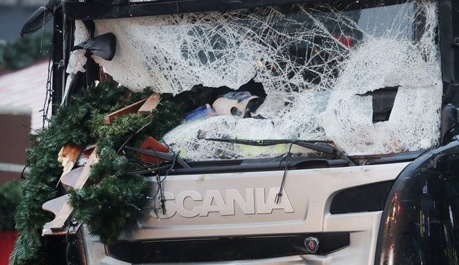 FILE - In this Dec. 20, 2016 file photo Christmas decoration sticks in the smashed window of the cabin of a truck which ran into a crowded Christmas market Monday evening killing several people in Berlin, Germany. Survivors and families of those killed in last year's Christmas market truck rampage in Berlin will meet with Chancellor Angela Merkel on Monday, Dec. 18, 2017 for the first time amid continued anger at German authorities' failure to stop the attack and handling of the aftermath. (AP Photo/Markus Schreiber, file)