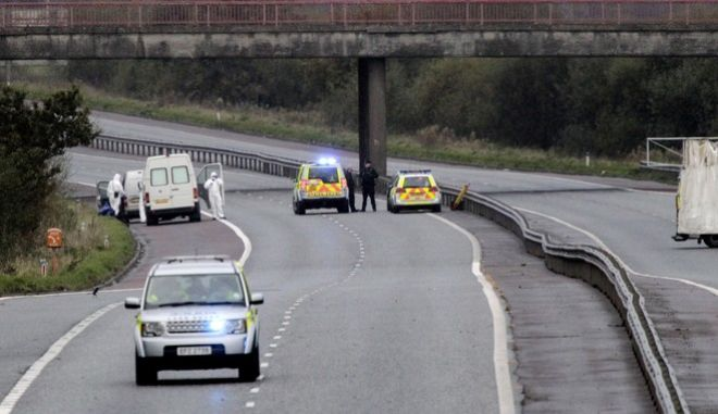 In this photo taken Thursday, Nov. 1, 2012, Police Service of Northern Ireland officers and forensics examine the scene of a fatal shooting on the M1 motorway near Lurgan, Northern Ireland. Northern Ireland police arrested two suspected Irish Republican Army militants Friday, Nov. 2, 2012 on suspicion of killing an off-duty prison officer, a rare slaying that has inspired political condemnation across Britain and Ireland. (AP Photo/Peter Morrison)