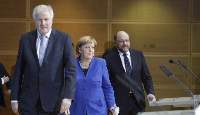 German Chancellor Angela Merkel is flanked by Bavarian governor Horst Seehofer, left, and Social Democratic Party Chairman Martin Schulz as they arrive for a joint statement after the exploratory talks between Merkel's Christian Democratic block and the Social Democrats on forming a new German government in Berlin, Germany, Friday, Jan. 12, 2018. (AP Photo/Michael Sohn)