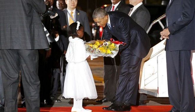U.S. President Barack Obama receives flowers from a girl as he arrives aboard Air Force One at Jomo Kenyatta International Airport in Nairobi July 24, 2015.  REUTERS/Jonathan Ernst