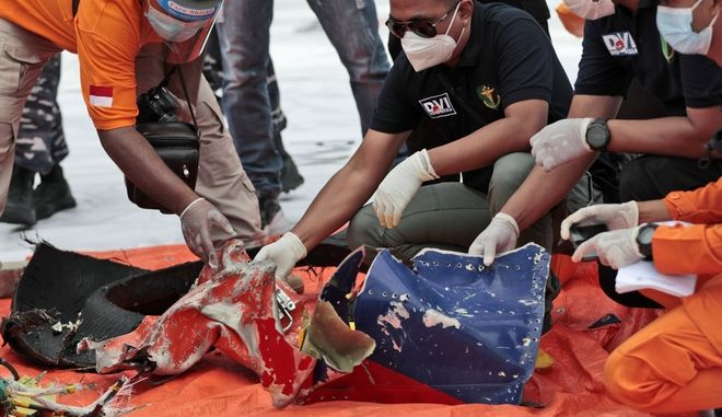 Investigators inspect debris found on the waters off Java Island around where a Sriwijaya Air passenger jet crashed, at Tanjung Priok Port in Jakarta, Indonesia, Sunday, Jan. 10, 2021. Indonesian rescuers pulled out body parts, pieces of clothing and scraps of metal from the Java Sea early Sunday morning, a day after a Boeing 737-500 with dozens of people onboard crashed shortly after takeoff from Jakarta, officials said. (AP Photo/Dita Alangkara)