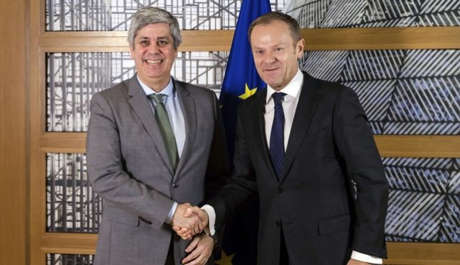 EU Council President Donald Tusk, right, welcomes Eurogroup President Mario Centeno upon his arrival at his office at the EU Council in Brussels on Monday, Jan. 22, 2018. (AP Photo/Geert Vanden Wijngaert)