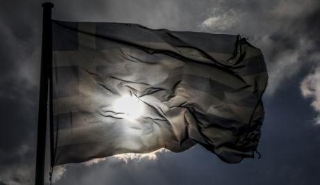 Ελληνική σημαία κυματίζει κάτω από τον συννεφιασμένο ουρανό της πόλης των Τρικάλων