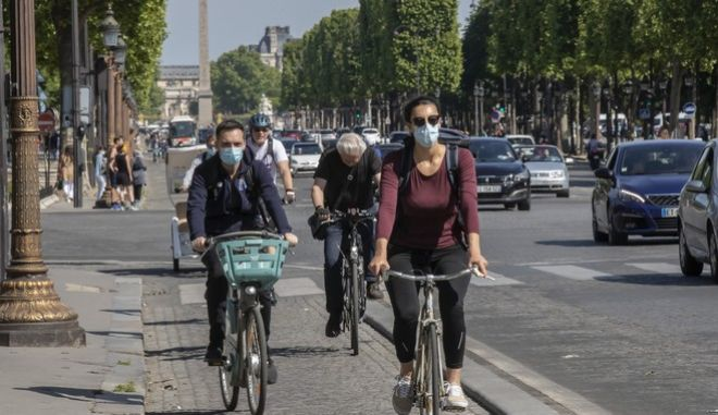 People wear face masks to help curb the spread of the coronavirus ride their bikes along the Champs Elysees avenue in Paris, Saturday, May 16, 2020, as France gradually lifts its Covid-19 lockdown. Parisians enjoying their first Saturday in the sun since travel and movement restrictions were lifted. (AP Photo/Michel Euler)